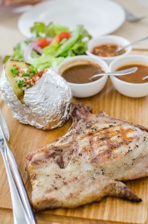 Grilled pork chop steak set with vegetables and sauce photo