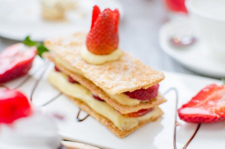 mille: Mille feuille, puff pastry layered with strawberries and whipped cream in Tea set Stock Photo