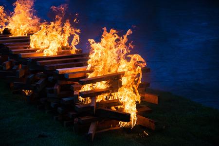 smolder: Camp fire burning wood on grass field