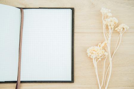 flores secas: Línea de papel de cuaderno abierto en el fondo de textura de madera con decoración de flores secas Foto de archivo