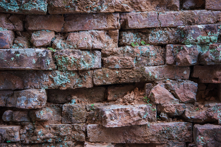 exterior architectural details: Old and broken red stone brick wall, close up details background Stock Photo