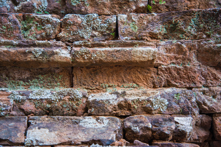 broken wall: Old and broken red stone brick wall, close up details background Stock Photo