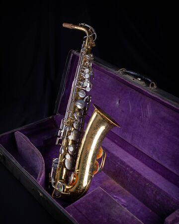 Alto Sax, Gold Lacquered in Deep Purple Velvet-Lined Hard Case side 1 on black background Stock fotó
