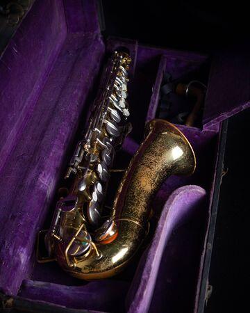 Buescher Alto Sax, Gold Lacquered in Deep Purple Velvet-Lined Hard Case in case on black background Stock fotó