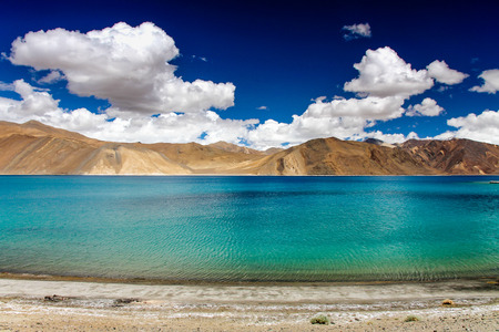 Blue and Turquoise Lake with Mountains in the Back and Deep Blue Sky - Pangong Lake, Ladakh, India photo