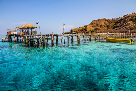 Amazing Arrival Wooden Jetty with Turquoise Blue Water, Brown Reef and Clear Sky-Kanawa Island,Flores,Indonesia Stock Photo