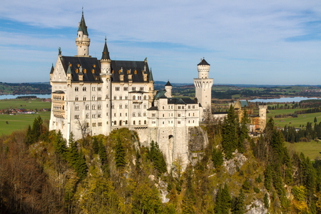 Neuschwanstein Castle in Autumn Sunny Day with Forest - Neuschwanstein, Germany photo