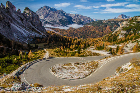 Winding road within Colorful Autumn Forest, Cloudy Blue Sky and Mountains-Dolomites,Italy
