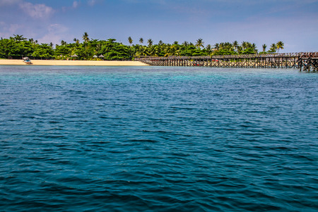 mabul: Mole on the empty beach with blue sky and palm trees in the back- Mabul Island,Celebes Sea, Sabah, Borneo,Malaysia,Asia Stock Photo