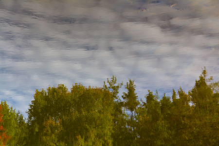 detai: Reflection of scattered white clouds,blue sky and green trees in the water-Trebon,Czech Republic Stock Photo
