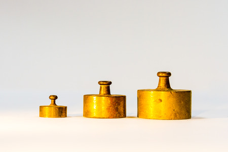 Collection of Thee Small Golden Vintage Iron Calibration Weights on White Background Stock Photo