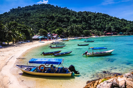 perhentian: Turquoise Sea and Tranquil Empty Beach with Deep Blue Sky, Many Boats and Palm Trees - Malaysia Editorial