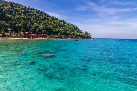 perhentian: Turquoise Sea with Palm Trees and Deep Blue Sky in the Backgrounbd - Perhentian Islands, Malaysia Stock Photo