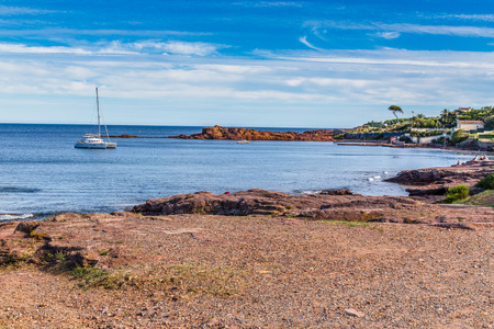 massif: Beach And Village On Red Rocks of Esterel Massif During Sunny Day-French Riviera, Provence-Alpes, Cote dAzur, France Stock Photo