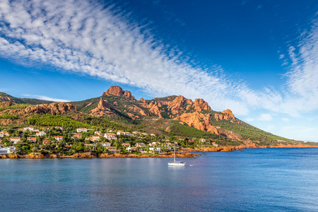 massif: Village And Trees Among Red Rocks of Esterel Massif During Sunny Day-French Riviera, Provence-Alpes, Cote dAzur, France Stock Photo