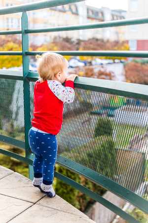 tiptoes: Little Boy Staying On The Tiptoes And Watching From The Balcony