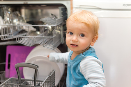 Adorable Little Blond Boy Putting Dishes Into The Dishwasher Stock Photo