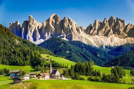 Santa Maddalena Church And Geisler (Odle) Dolomites Mountain Peaks  - Val Di Funes, South Tyrol, Italy Фото со стока