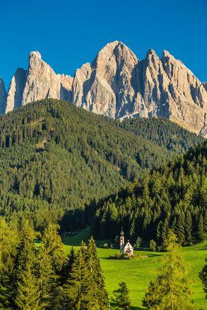 Church of St. John of Nepomuk And Geisler (Odle) Dolomites Peaks - Santa Maddalena, Val Di Funes, Tyrol, Italy Фото со стока