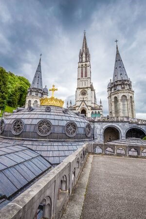 Towers Of Rosary Basilica And Gilded Crown - Sanctuary Of Our Lady Of Lourdes, Lourdes, Hautes-Pyrenees, Occitanie, France, Europe Stock Photo
