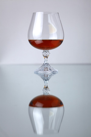 distilled alcohol: Glass of brandy over a grey background with reflection Stock Photo