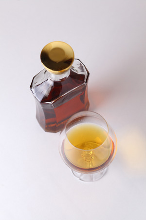 distilled alcohol: Glass of brandy over a white background with bottle