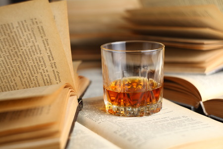 Glass of whiskey standing on several open books