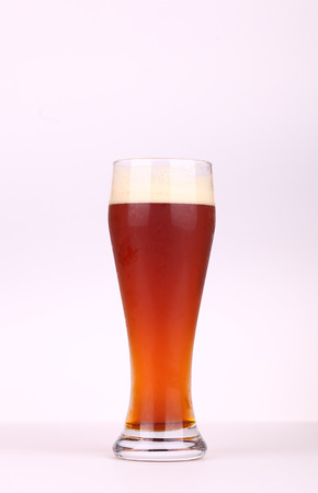 pilsner beer: Glass of brown ale over a white background