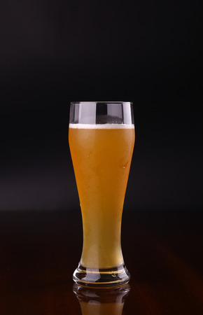 pilsner beer: Glass of wheat bear over a dark background