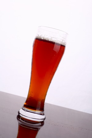 ale: Glass of brown ale over a white background