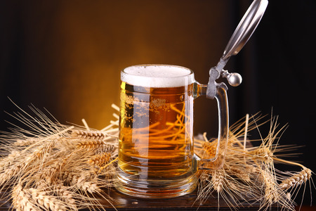 Mug of light beer on a wooden chest with barley ears photo