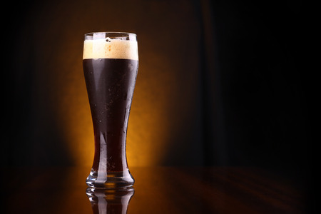 Tall glass of dark beer over a dark background lit yellow photo