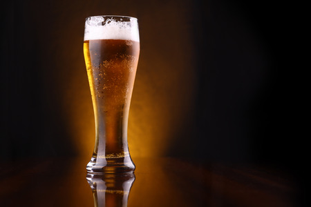 beer background: Tall glass of light beer on a dark background lit yellow Stock Photo