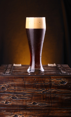 Tall glass of dark beer standing on a wooden chest photo