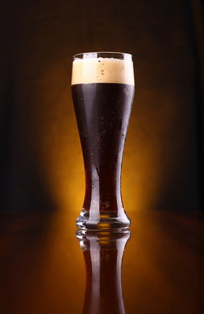 Tall glass of dark beer over a dark background lit yellow Stock Photo