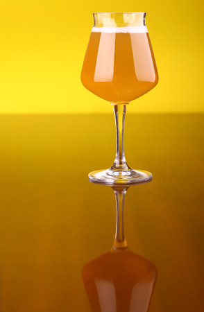 snifter: Snifter glass with wheat beer over a bright yellow background Stock Photo