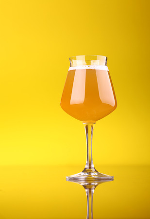Snifter glass with wheat beer over a bright yellow background Stock Photo