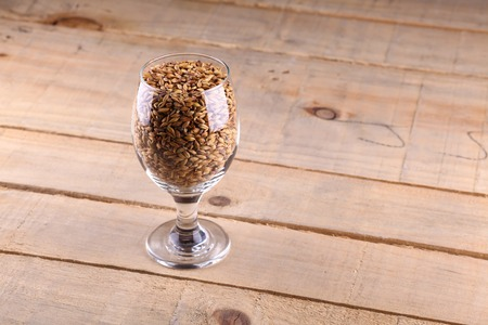 barley malt: Glass full of barley malt over a wooden background
