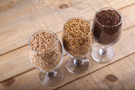 types of glasses: Glasses filled with different types of malt over a wooden background