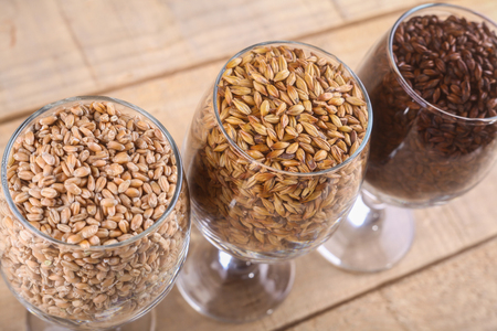 Glasses filled with different types of malt over a wooden background