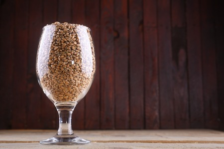Glass full of light wheat malt over a wooden background