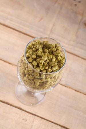 pellets: Glass full of hop pellets over a wooden background