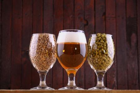 Verres de bière, de malt et de houblon sur un fond en bois Banque d'images