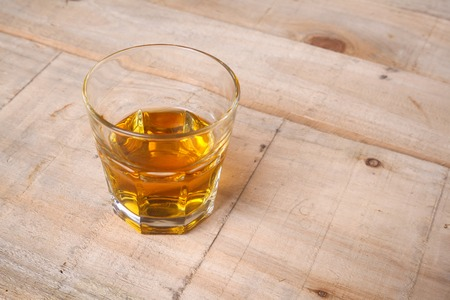 distillate: Tumbler glass with whiskey on a grunge wooden table