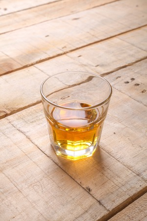 tumbler: Tumbler glass with whiskey on a grunge wooden table