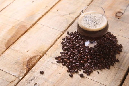 stout: Snifter glass with coffee stout surrounded by roasted coffee beans over a grunge wooden background
