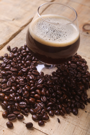 cerveza negra: Vidrio del trago de caf� con cerveza negra rodeada de granos de caf� tostados sobre un fondo de madera del grunge Foto de archivo