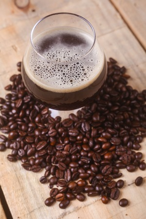 cerveza negra: Snifter glass with coffee stout surrounded by roasted coffee beans over a grunge wooden background