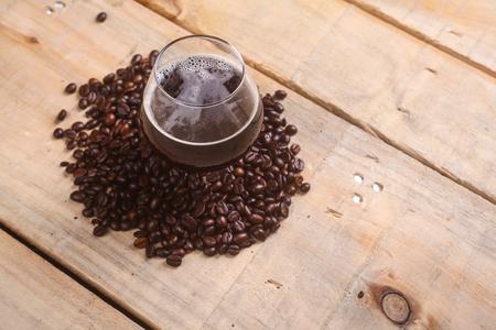 cerveza negra: Vidrio del trago de café con cerveza negra rodeada de granos de café tostados sobre un fondo de madera del grunge Foto de archivo