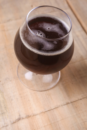 cerveza negra: Snifter glass with dark stout beer on a grunge wooden table